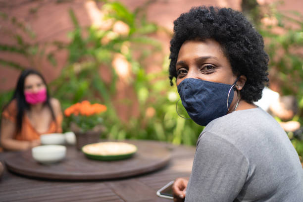 portrait of woman using protective mask in the backyard - friends on background - afro latino mask imagens e fotografias de stock