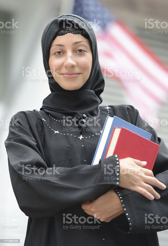 Portrait of woman wearing head scarf holding books. stock photo