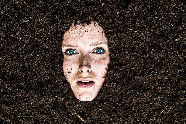 portrait of woman who is buried in a garden - gömülü stok fotoğraflar ve resimler