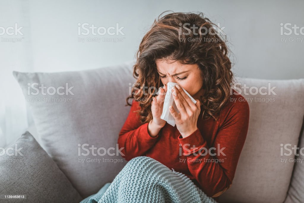 Portrait of woman with allergy blowing her nose. Illness And...