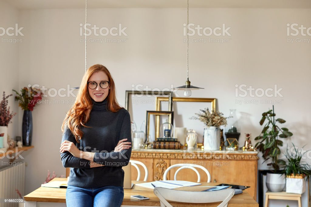 Portrait of smiling woman leaning on table. Young female is relaxing...