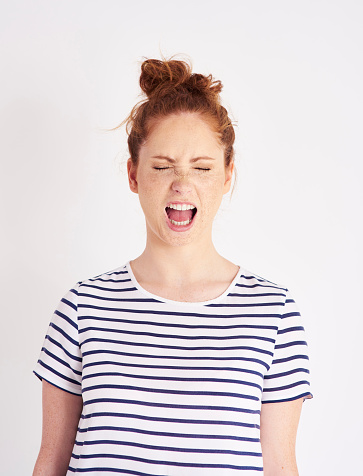 487960859 istock photo Portrait of woman with closed eyes shouting at studio shot 1023928614