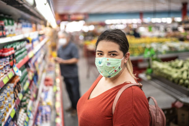 Portrait of woman with disposable medical mask shopping in supermarket stock photo