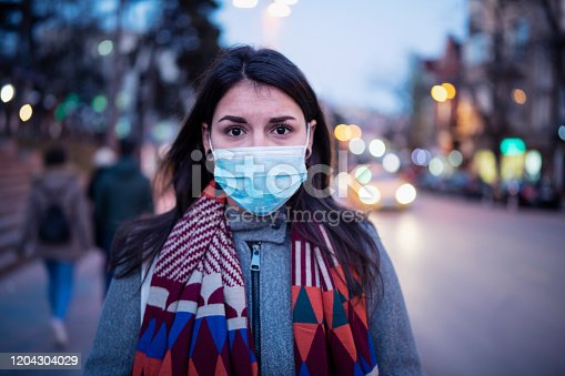 Close up portrait of Latino young woman on the street, she walking on the street with protective face mask and looking at camera, she looking sick and scared.