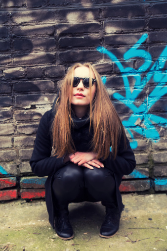 portrait of woman with ginger hair wearing sunglasses on graffiti background