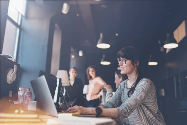 Portrait of woman with laptop at workplace stock photo