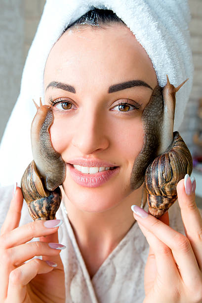 portrait of  woman with snails on her face stock photo