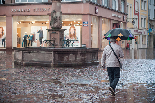 portrait of woman with umbrella on cobbles place with fountain in the city