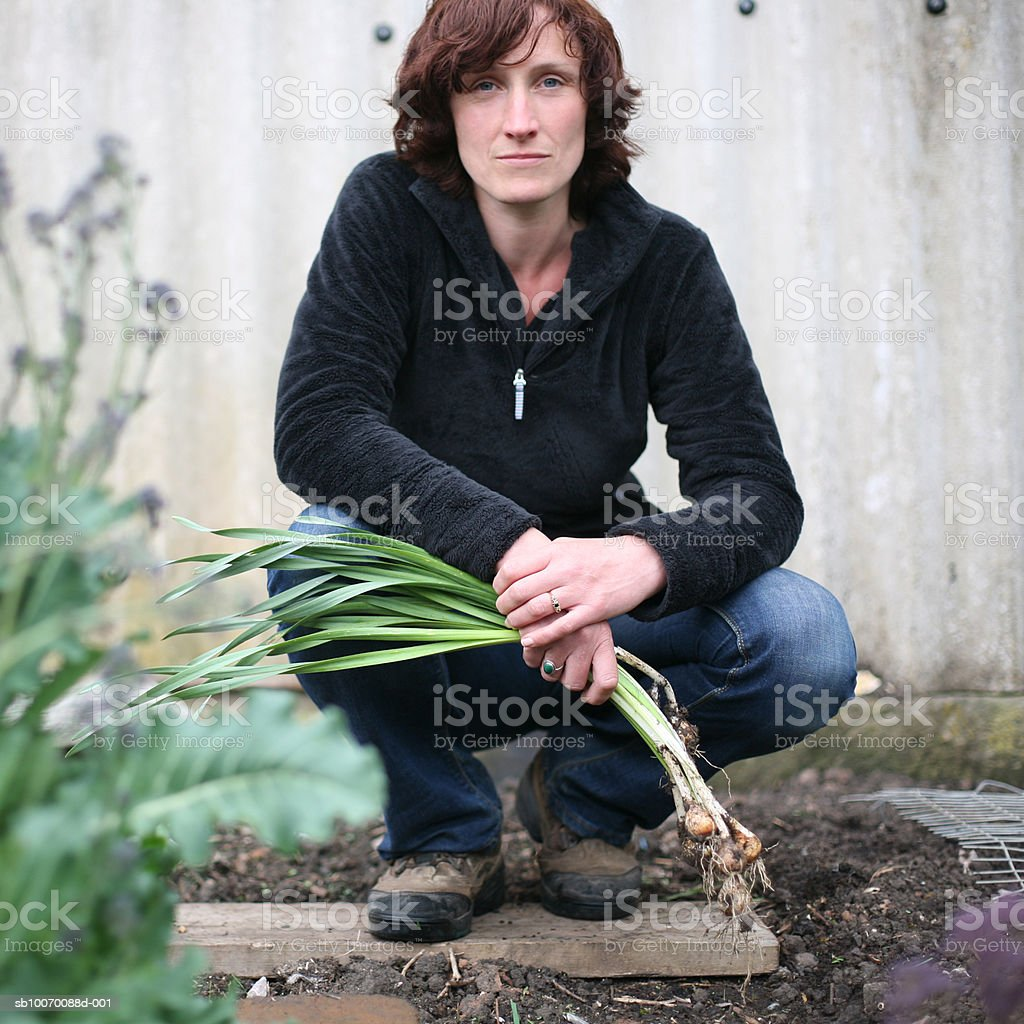 Portrait of woman with vegetables crouching in garden royalty-free stock photo