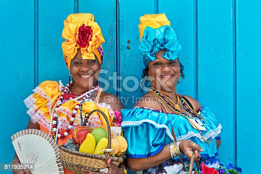 Portrait of happy Cuban women standing against blue wooden wall. Smiling mature women are in traditional dresses. They are with fruit basket and hand fan.