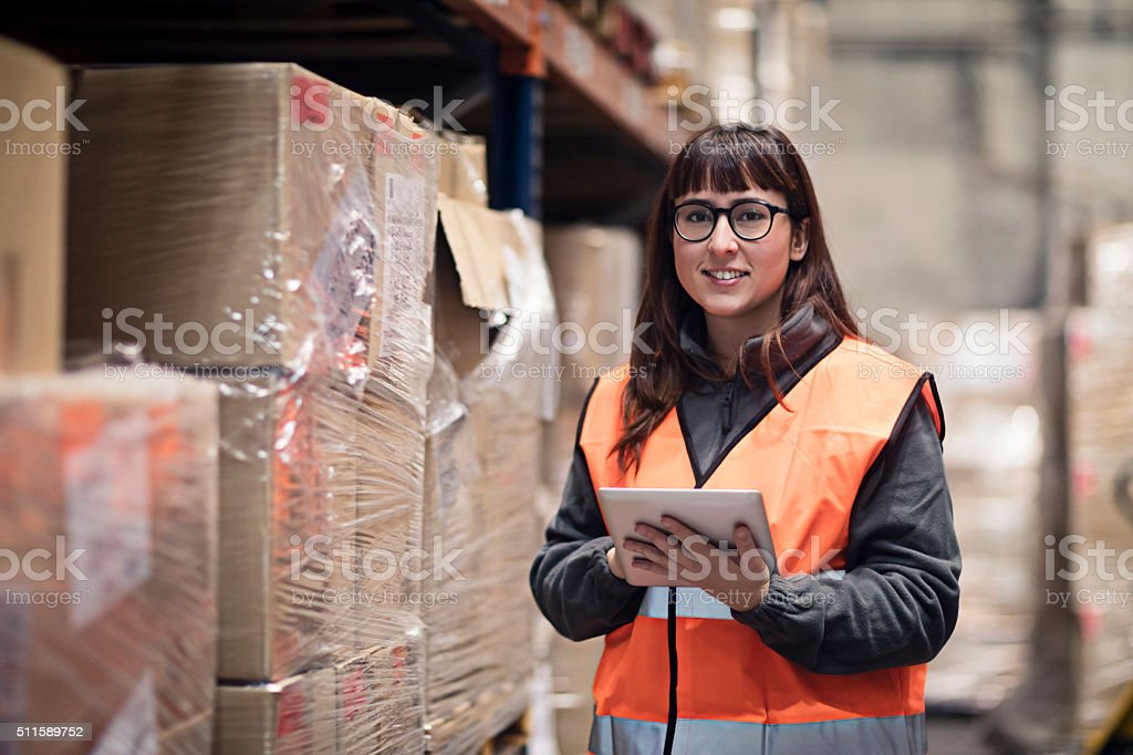 Portrait of worker checking box in warehouse stock photo