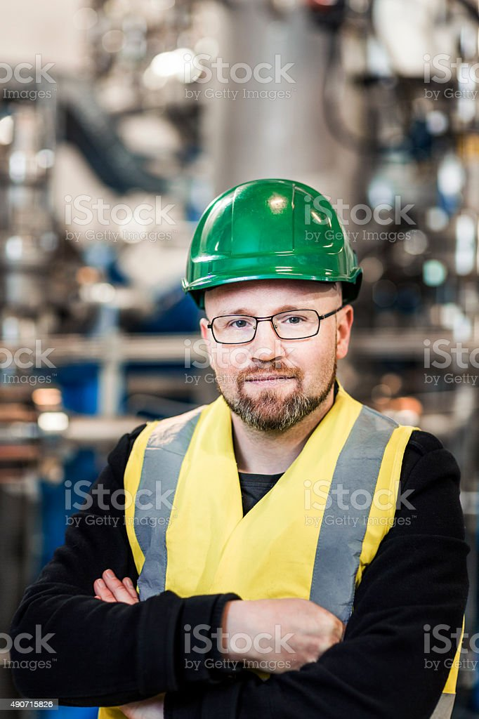 Portrait of worker standing with arms crossed in industry stock photo