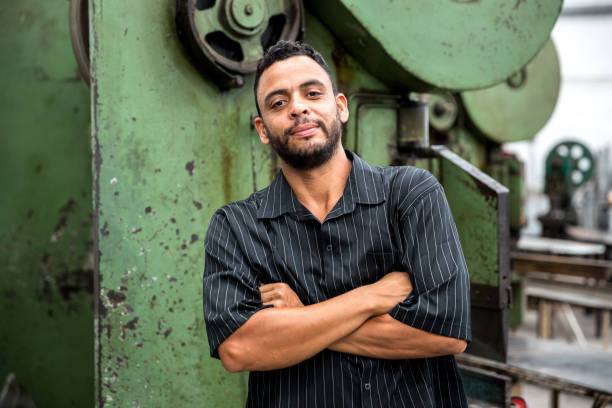 portrait of worker with his arms crossed at factory - characters stock pictures, royalty-free photos & images