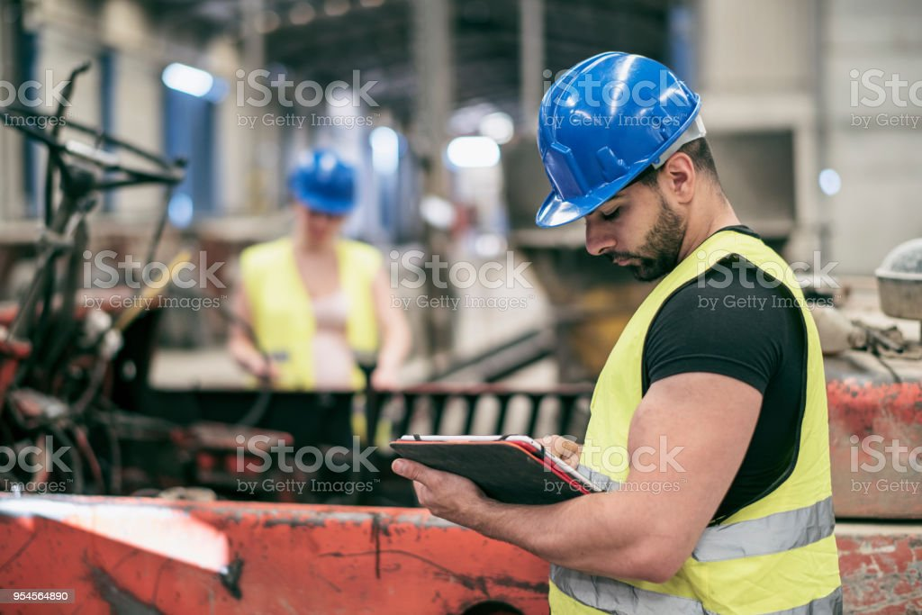 Portrait of worker with tablet and woman in background stock photo
