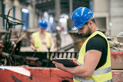 Portrait Of Worker With Tablet And Woman In Background Stock Photo - Download Image Now