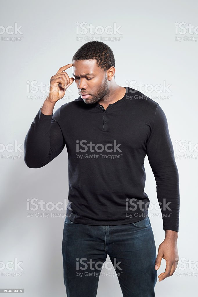 Portrait of worried afro american young man Portrait of worried afro american young man wearing in black, standing against grey background with eyes closed. Adult Stock Photo