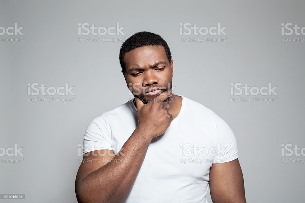 Portrait of worried afro american young man Portrait of pensive afro american young man wearing white t-shirt, standing against grey background with hand on chin. Adult Stock Photo