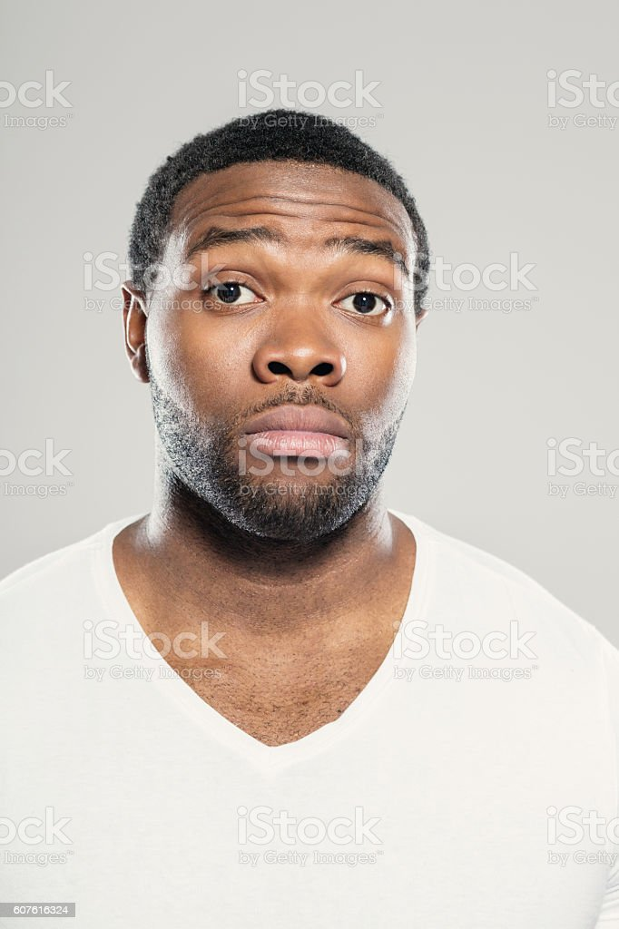 Portrait of worried afro american young man Portrait of worried afro american young man wearing white t-shirt, standing against grey background, looking at camera. Adult Stock Photo