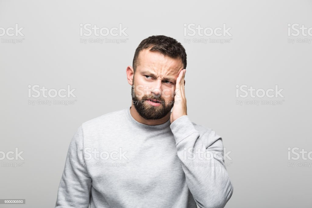 Portrait of worried bearded young man havign problem Portrait of worried bearded young man looking away with hand on cheek. Studio shot, grey background. 30-34 Years Stock Photo