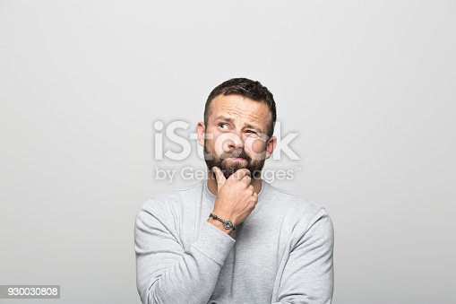 Portrait of worried bearded young man looking up with hand on chin. Studio shot, grey background.