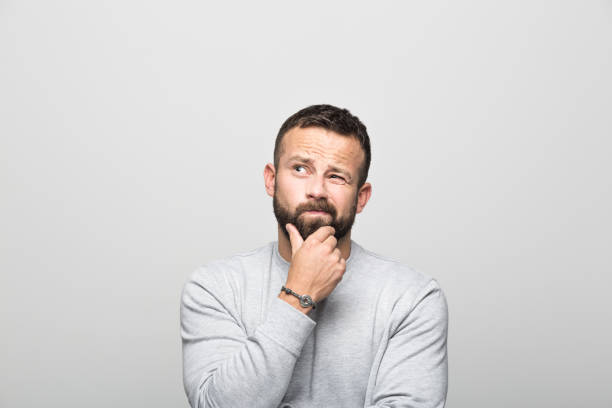 Portrait of worried bearded young man looking up with hand on chin picture id930030808?b=1&k=6&m=930030808&s=612x612&w=0&h=4rn795f46c4nzg2fvugtbfs6nhjm0nyocbfnxtv3ici=