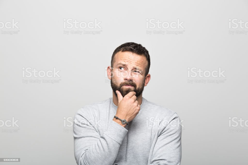 Portrait of worried bearded young man looking up with hand on chin stock photo