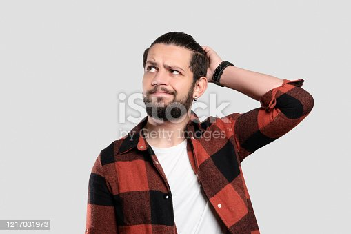 836798276 istock photo Portrait of worried bearded young man looking up with hand on head 1217031973