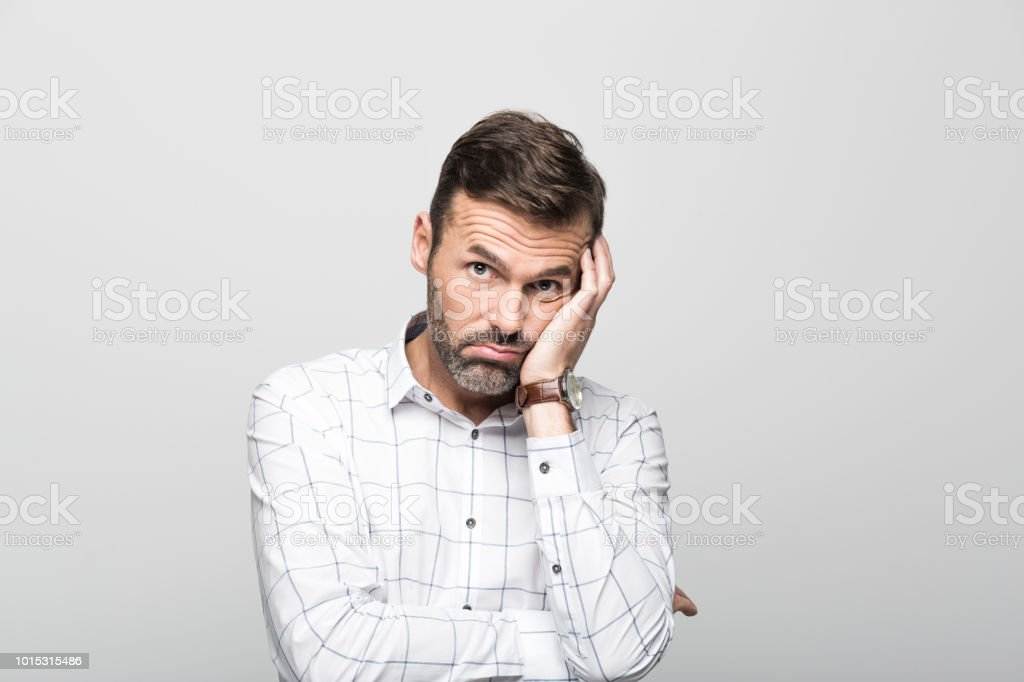Portrait of worried businessman, grey background Portrait of worried businessman wearing white shirt, standing with hand on cheek against grey background. Studio shot. 30-39 Years Stock Photo