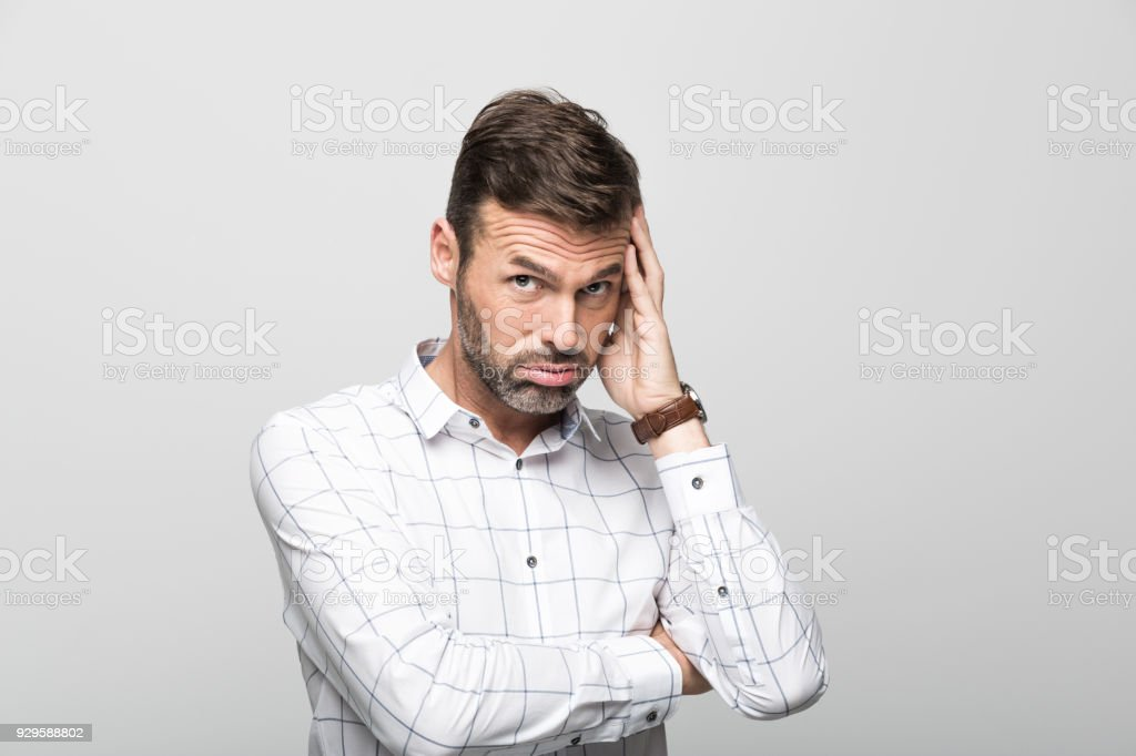 Portrait of worried businessman, grey background Studio portrait of worried businessman wearing white shirt, standing with hand on head against grey background. 30-39 Years Stock Photo