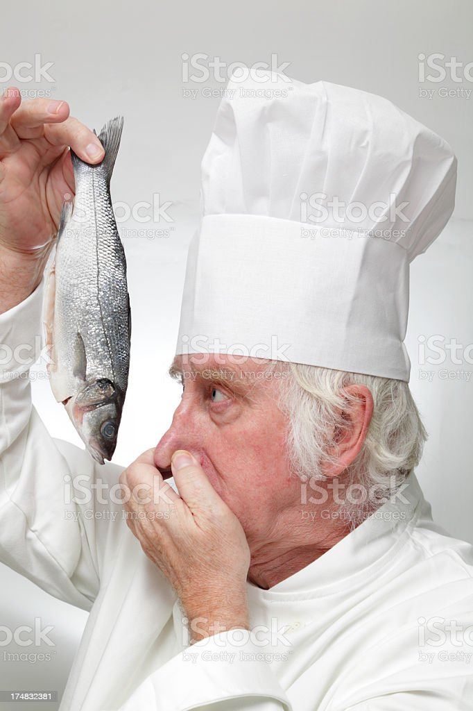 portrait of worried chef smelling fish on plain background royalty-free stock photo