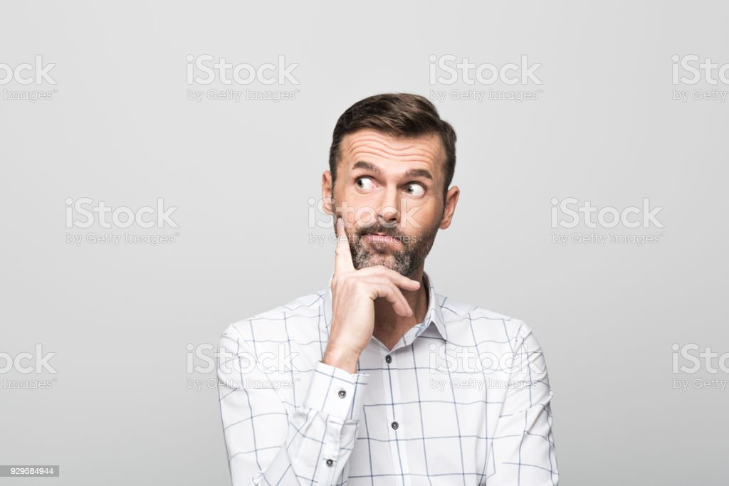 Portrait of worried, handsome man, grey background Studio portrait of worried, handsome businessman wearing white shirt, standing with hand on chin against grey background. 30-39 Years Stock Photo