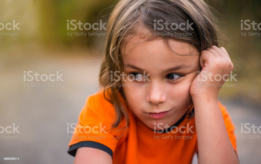 Portrait of worried little girl thinking with negative facial ex stock photo