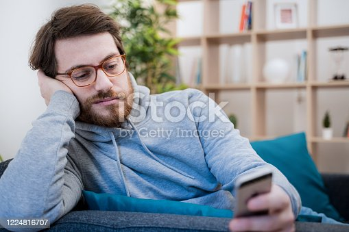 Single lonesome man checking mobile phone on the couch