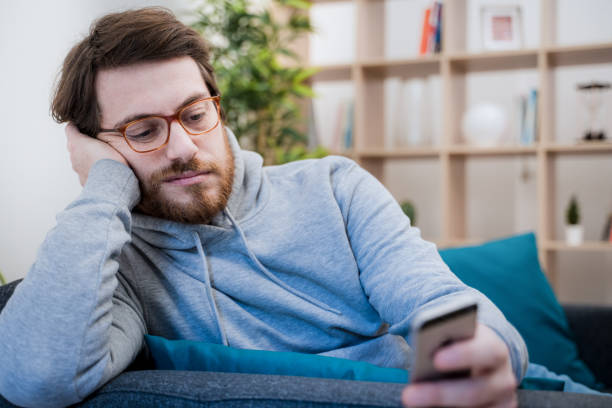 Portrait of worried man on the sofa holding cellphone at home stock photo