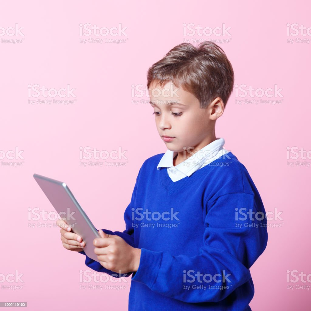 Portrait of worried schoolboy using a digital tablet Worried schoolboy wearing school uniforms using a digital tablet. Studio shot, pink background. 8-9 Years Stock Photo