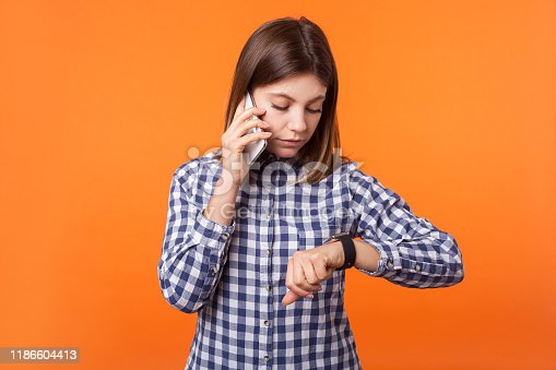640046924 istock photo Portrait of worried young woman with brown hair wearing checkered shirt talking on phone. indoor studio shot isolated on orange background 1186604413