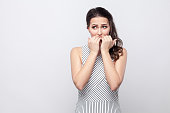 istock Portrait of worry beautiful young brunette woman with striped dress standing, looking away and bitting her nails with stressed face 1090545072