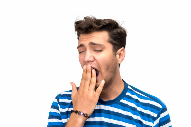 Portrait of yawning young man over white background