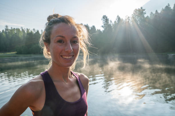 Portrait of yoga girl on lake pier at sunrise smiling stock photo