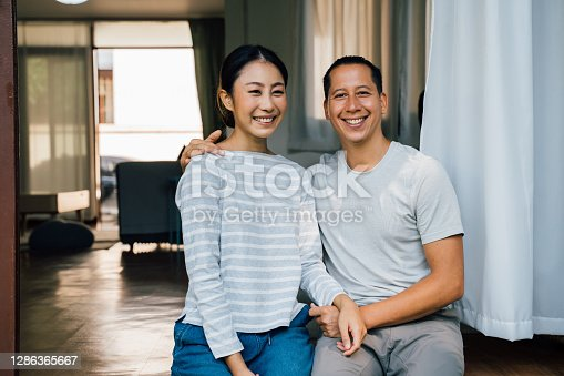 Portrait of young adult Asian couple embracing together with home interior in background. 30s happy mature husband and wife smiling and looking at camera. Marriage and happy relationship life concept