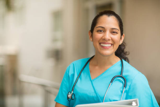 Portrait of young adult female healthcare professional stock photo Smiling female healthcare professional looks at the camera while in hospital hallway. She is standing with her arms crossed. latin american and hispanic ethnicity stock pictures, royalty-free photos & images