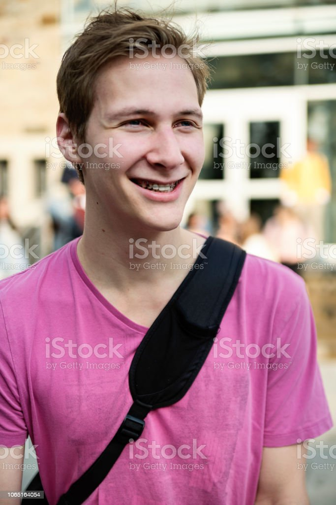 Portrait of young adult man student in front of College. stock photo