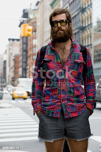 Portrait of young adult man with beard in downtown city, New York City