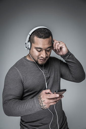 SYD11207: Portrait of young adult pacific islander man with headphones looking and listening to mobile device