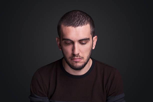 portrait of young adult with sad expression - guardare verso il basso foto e immagini stock