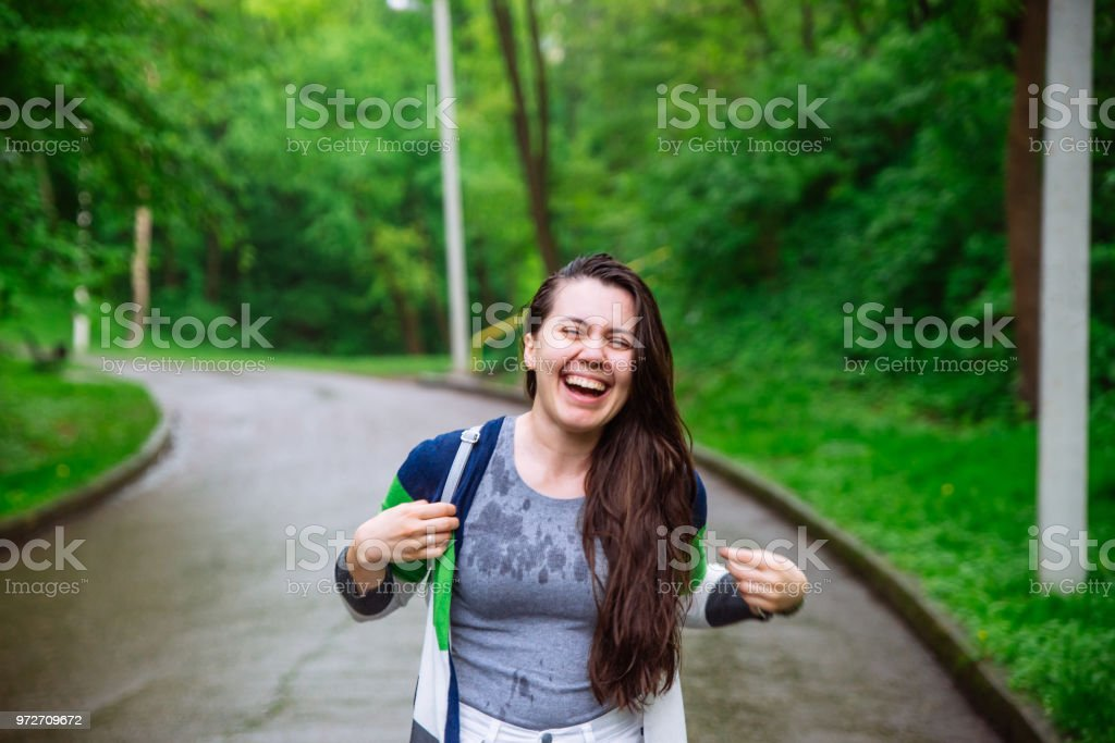 portrait of young adult woman wet after rain. smiling stock photo
