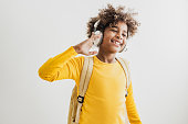 Studio shot of young African American girl with backpack and headphones on the white background