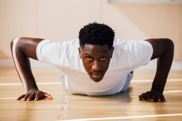 Portrait of young African American man doing push-up on the floor stock photo