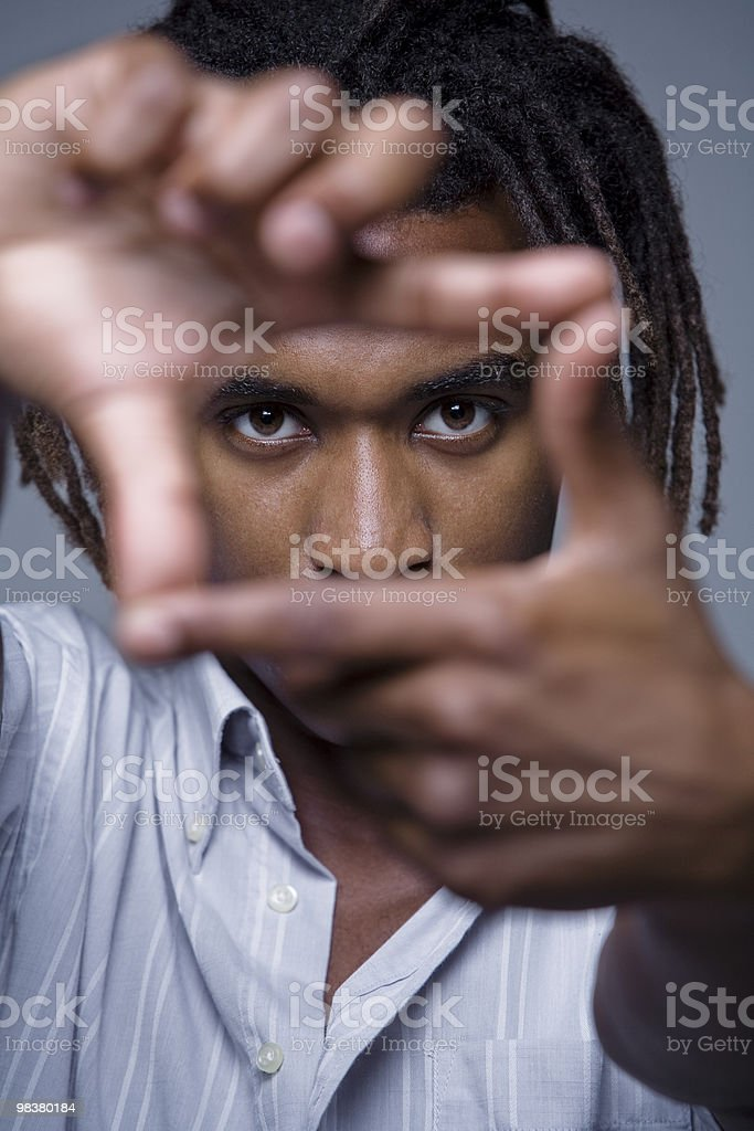 Portrait of young African American man looking through framed hands royalty-free stock photo