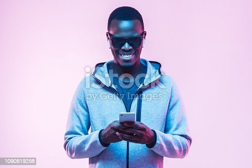 istock Portrait of young african american man using smartphone to listen music with earphones 1090819258